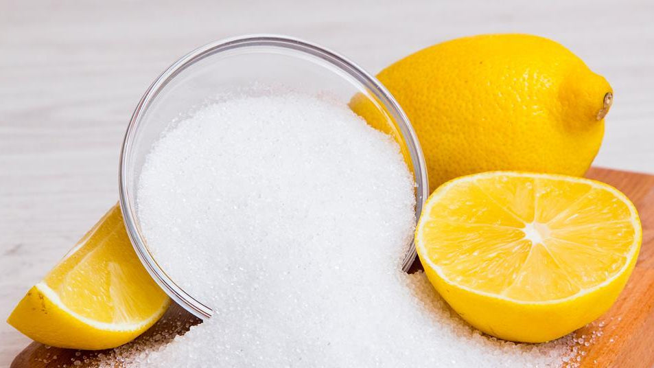 citric acid in bowl and lemons next to bowl.