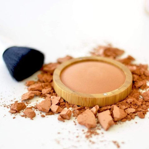 crushed and pressed natural glow powder with a make up brush laying next to it.