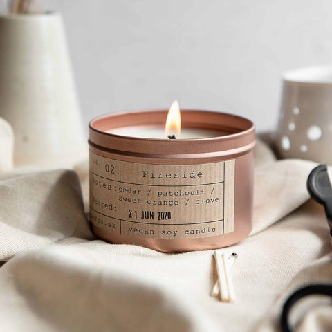 tiger and co candle in rose gold tin sitting on table surrounded by homeware bits.