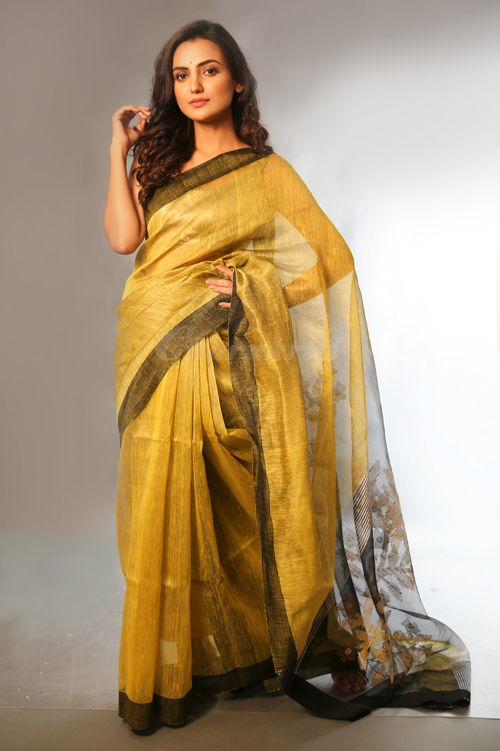 This Mustard Saree Is Handwoven With Linen And Silk Yarns And Features Black Border And Woven Floral Design Details On The Pallu Accented With Thread Tassel Details.