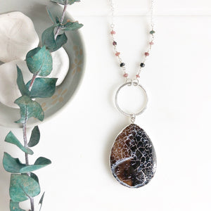 Long Earth Tone Crackle Teardrop and Ring Necklace in Silver with Beading Accents.