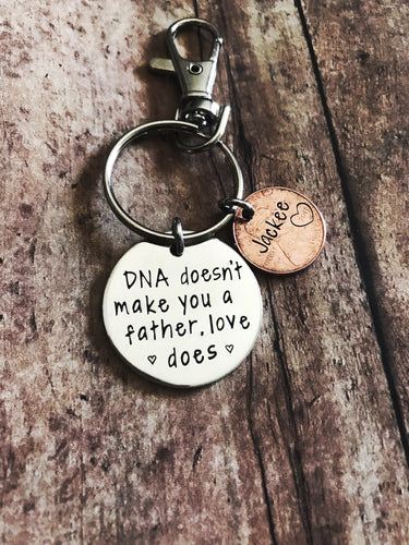 """DNA doesn't make you a dad"" keychain"