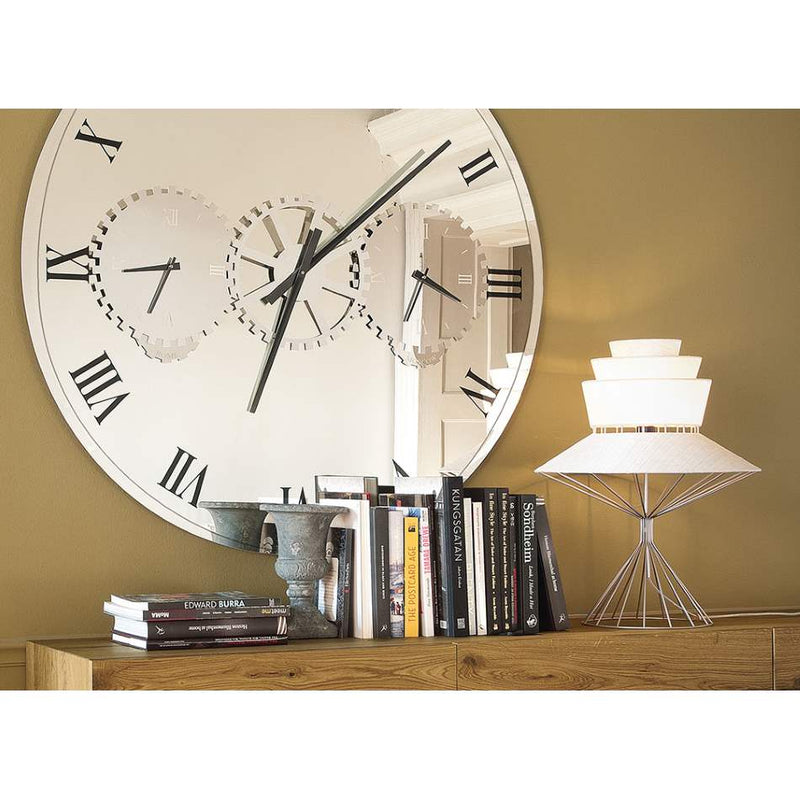 View of Times modern mirror wall clock placed behind a shelf of books.