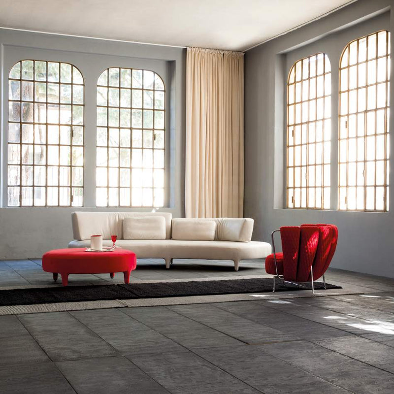 Delta Sagomato sofa with red foot stools nearby