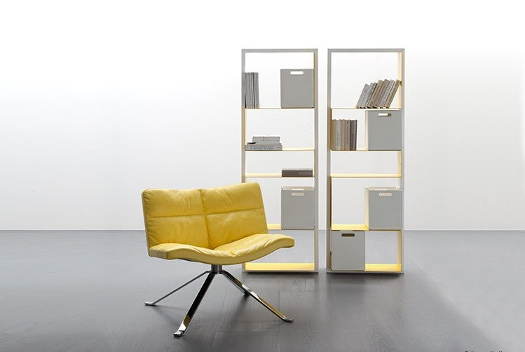 Wave Soft Chair in yellow leather with bookshelf behind it