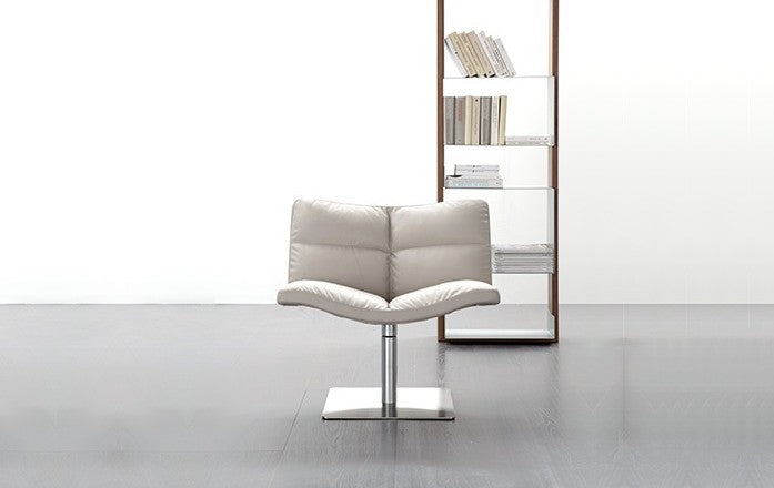 Wave Soft Chair in white leather with bookshelf behind it