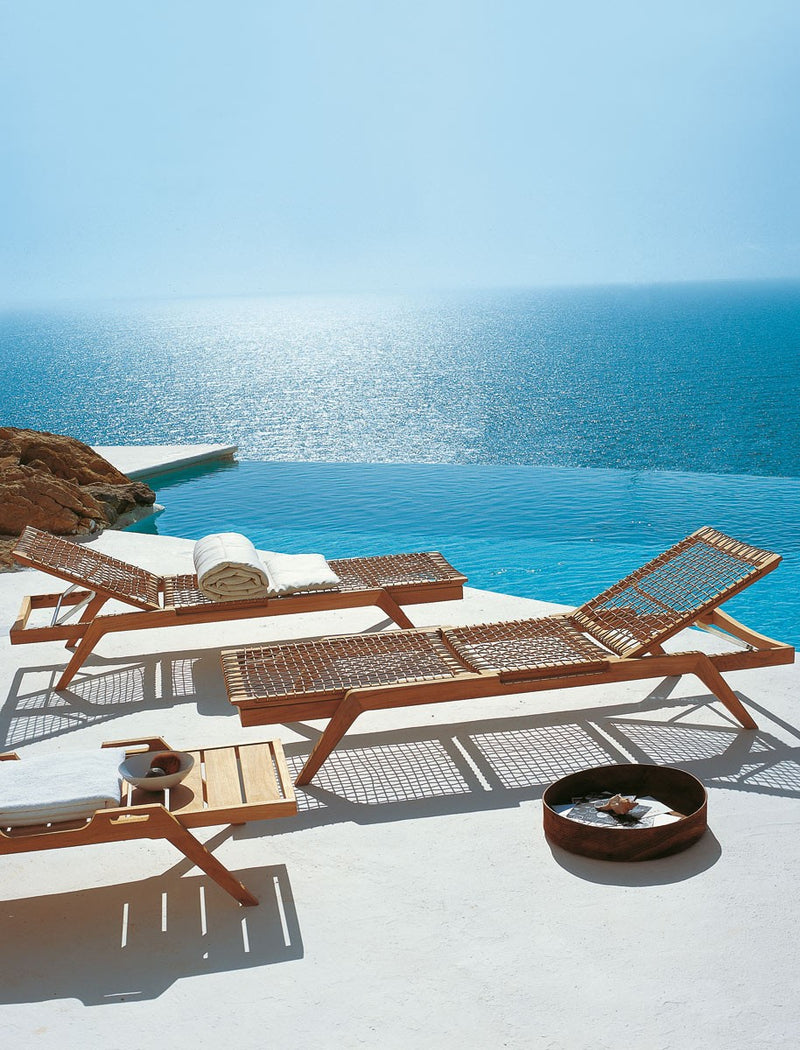 Synthesis Sun Lounger designed by Unopiú in Teak with Sun beaming onto the water