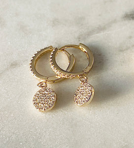 mini huggie earring with a pave disc charm hanging