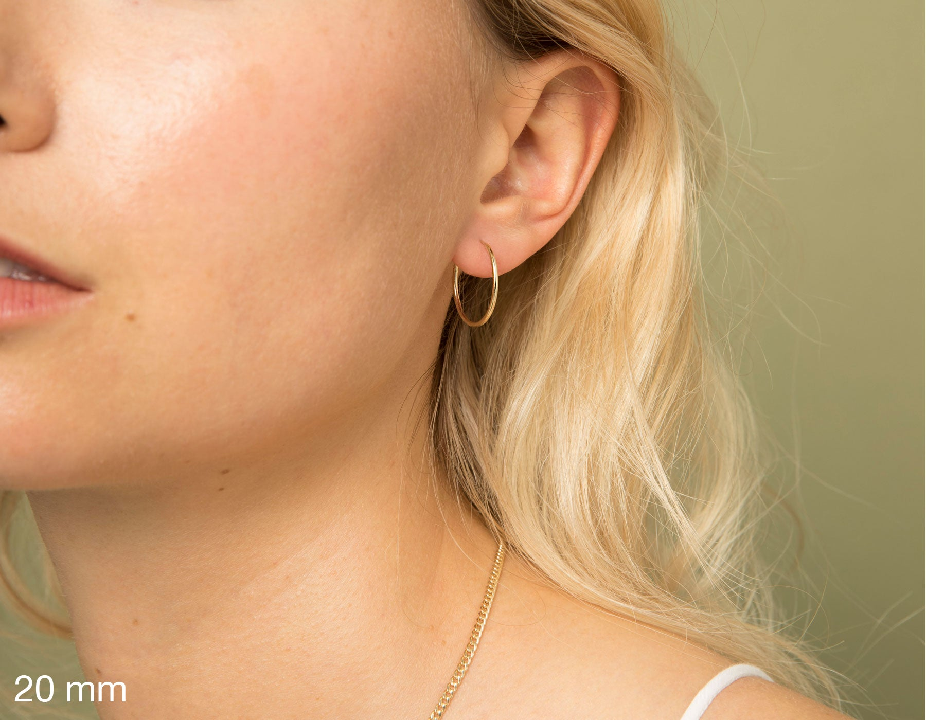 model wearing Vrai simple minimalist small hoop 14K yellow gold