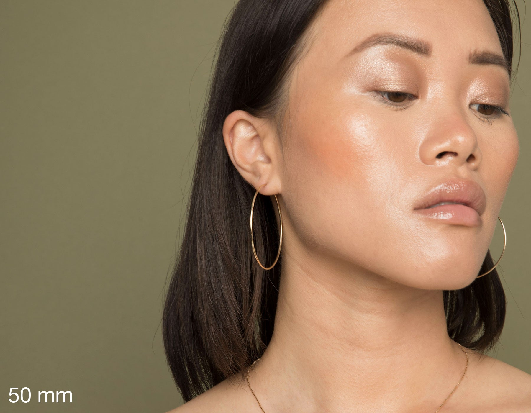 model wearing Vrai simple minimalist large hoop 14K yellow gold