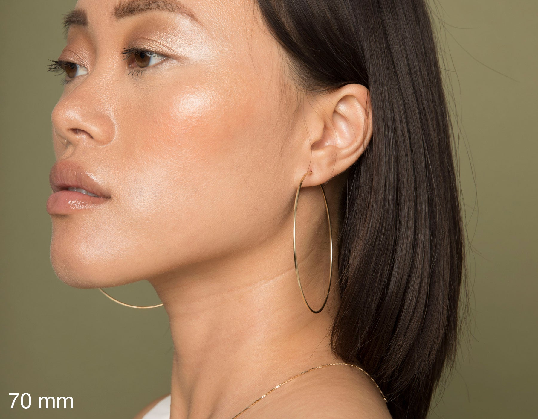 model wearing Vrai simple minimalist xlarge hoop 14K yellow gold