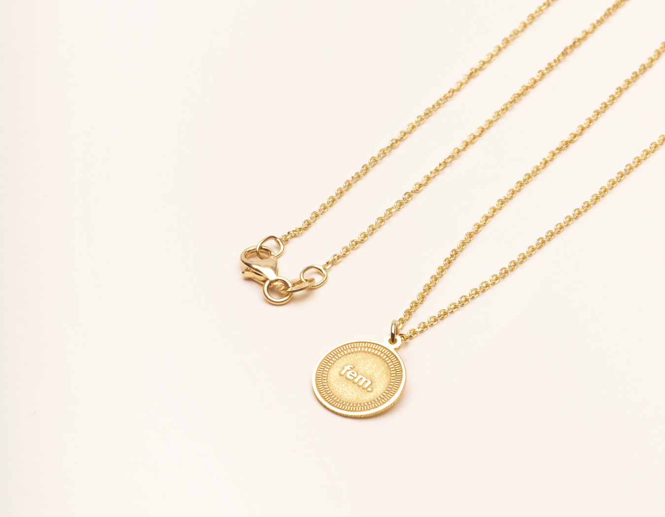 minimalist feminism 14k yellow gold Fem. Necklace circle pendant on thin chain with lobster clasp by Vrai and Oro