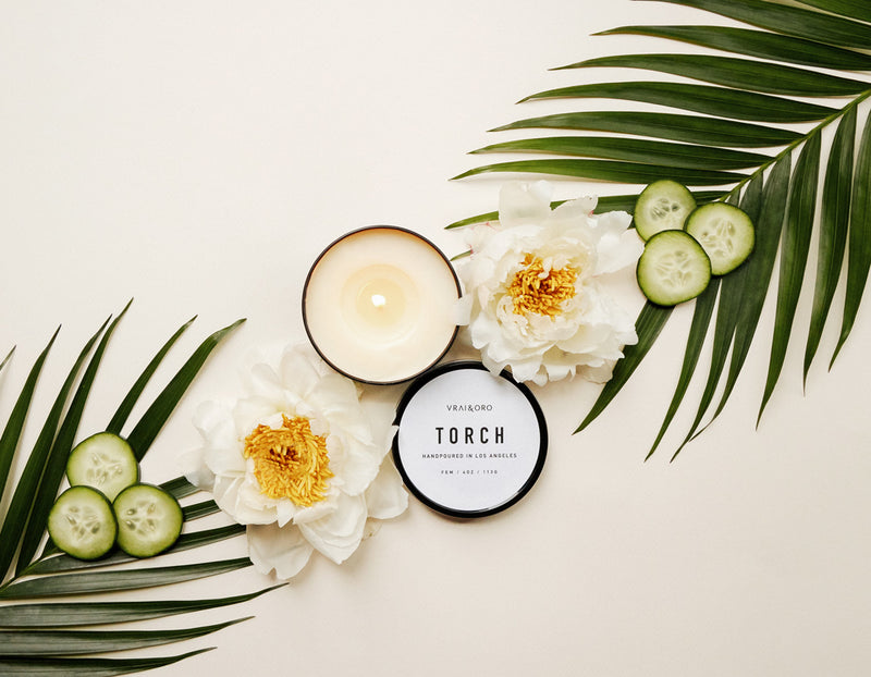 Hand crafted candle by Torch and Vrai & Oro surrounded by flowers and palm fronds