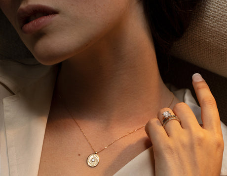 Model wearing VRAI Inner Light Medallion made with solid 14k yellow gold and sustainably created emerald diamond