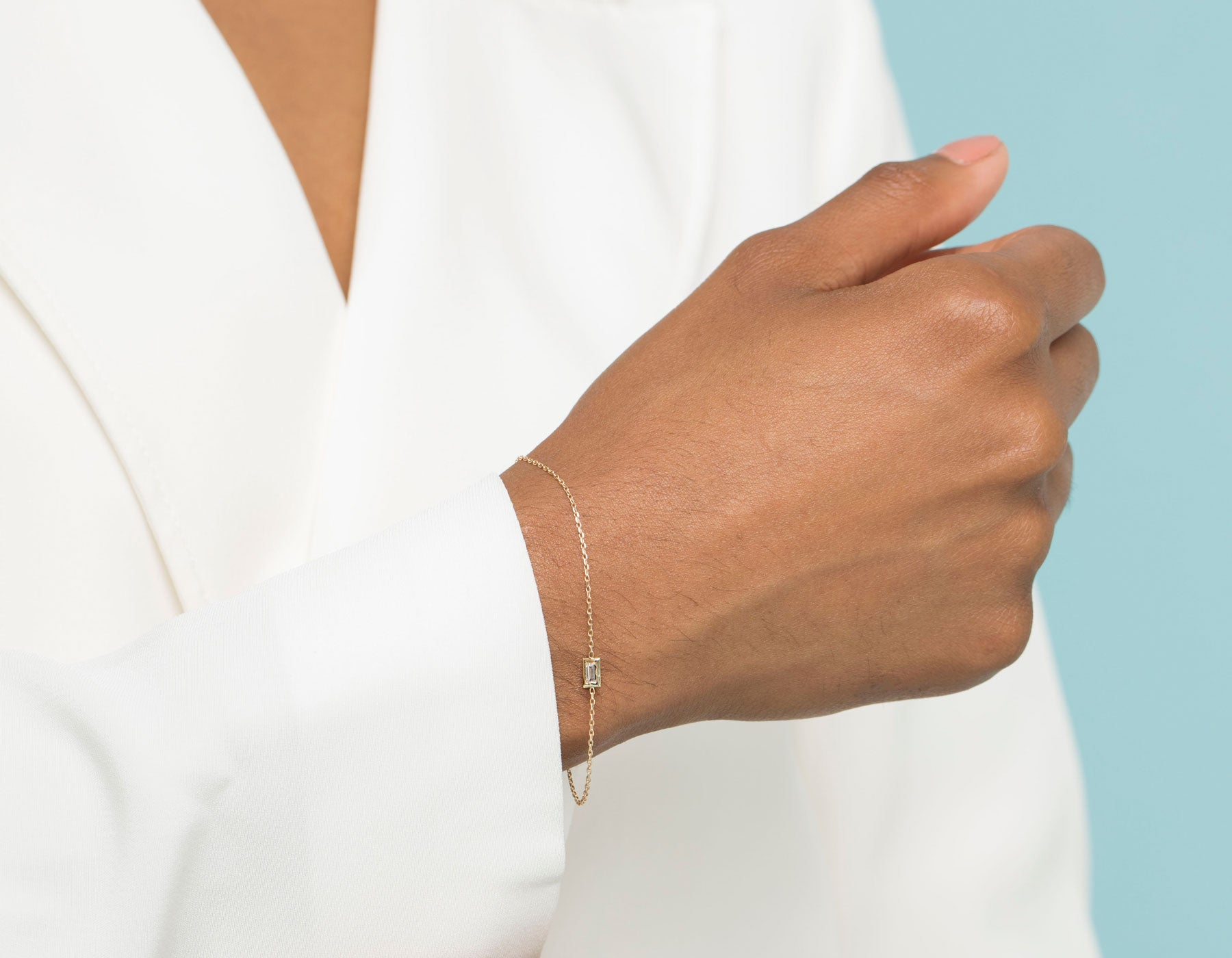 Model wearing dainty minimalist Baguette Diamond Bezel Bracelet by Vrai, 14K White Gold