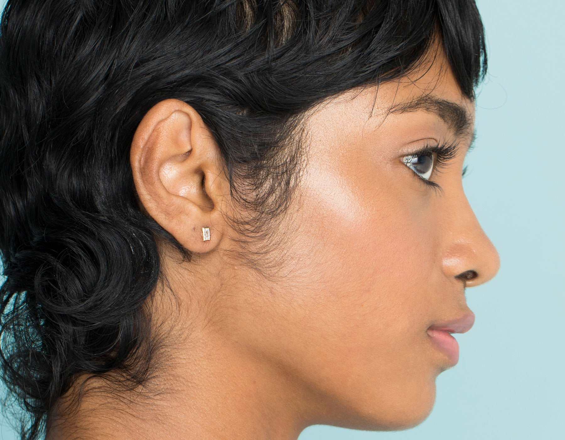Model wearing dainty minimalist Baguette Diamond Bezel Stud Earrings by Vrai in 14k solid gold