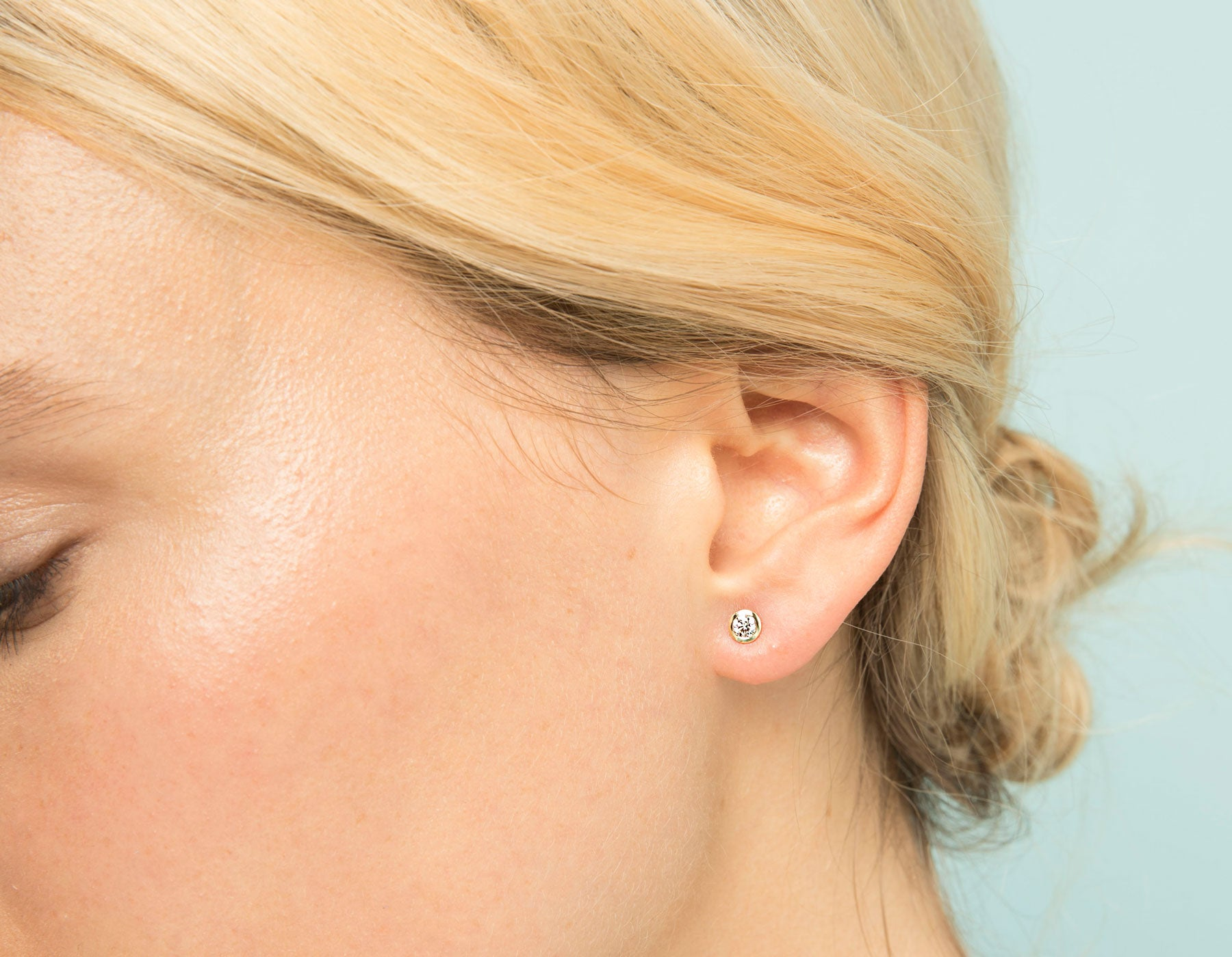 Model wearing dainty minimalist Round Diamond Bezel Earrings by Vrai in 14k solid gold