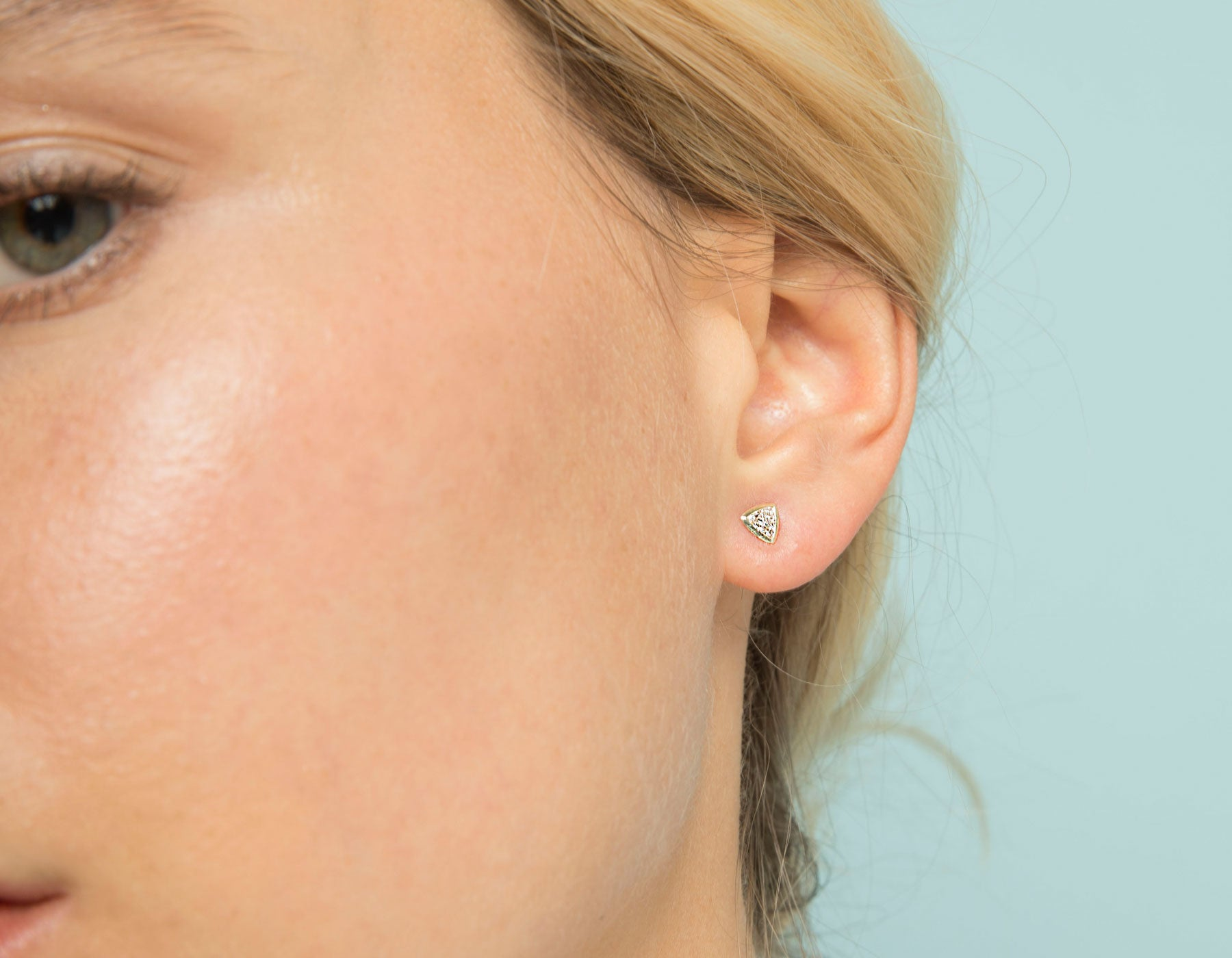 Model wearing dainty minimalist Trillion Diamond Bezel Earring by Vrai in 14k solid gold
