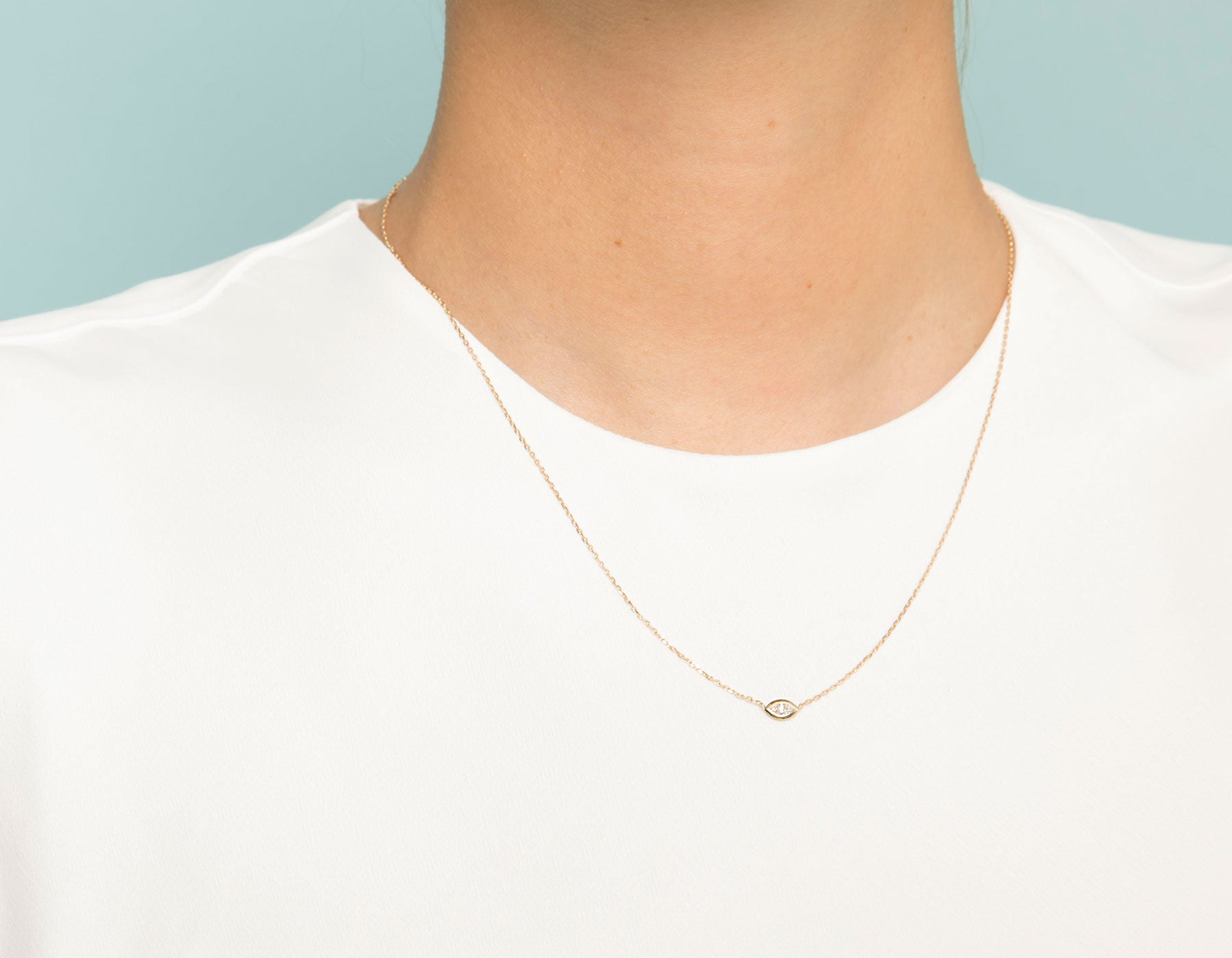 Model wearing dainty minimalist Marquise Diamond Bezel Necklace by Vrai, 14K Yellow Gold