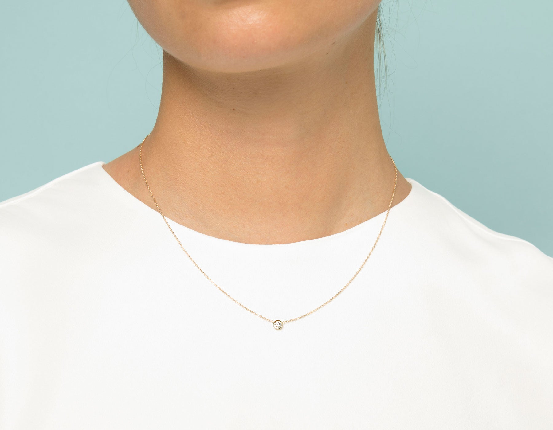 Model wearing dainty minimalist Round Diamond Bezel Necklace by Vrai, 14K Yellow Gold
