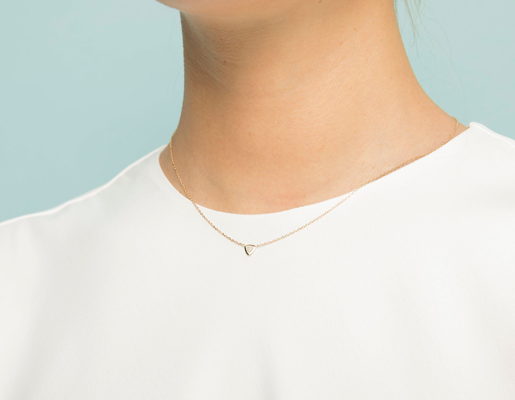 Model wearing dainty minimalist Trillion Diamond Bezel Necklace by Vrai, 14K White Gold