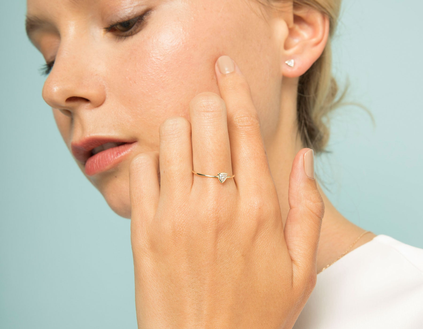 Model wearing dainty minimalist Trillion Diamond Bezel Ring by Vrai in 14k solid gold