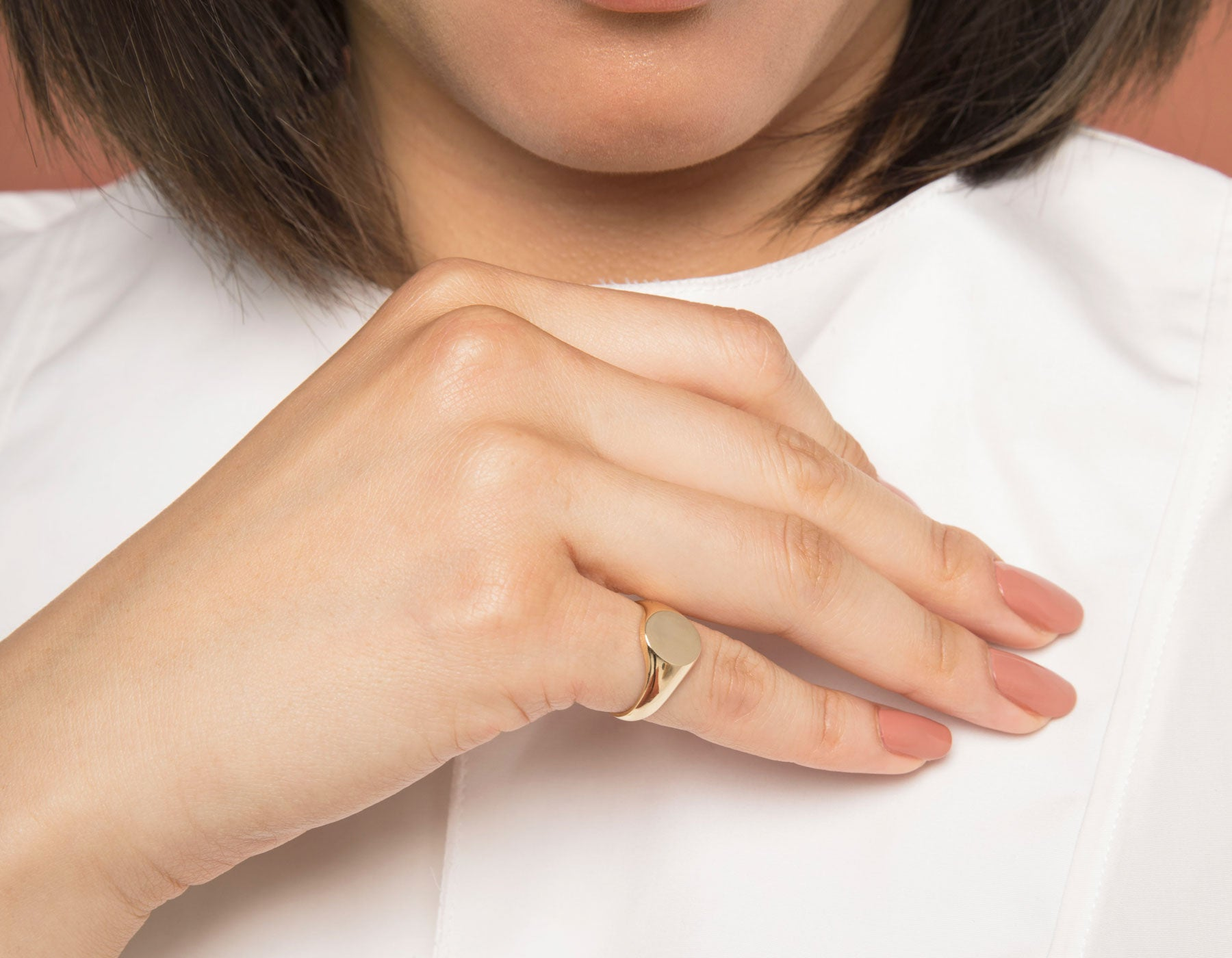 Model wearing Vrai 14k yellow gold signet ring with engraved initial