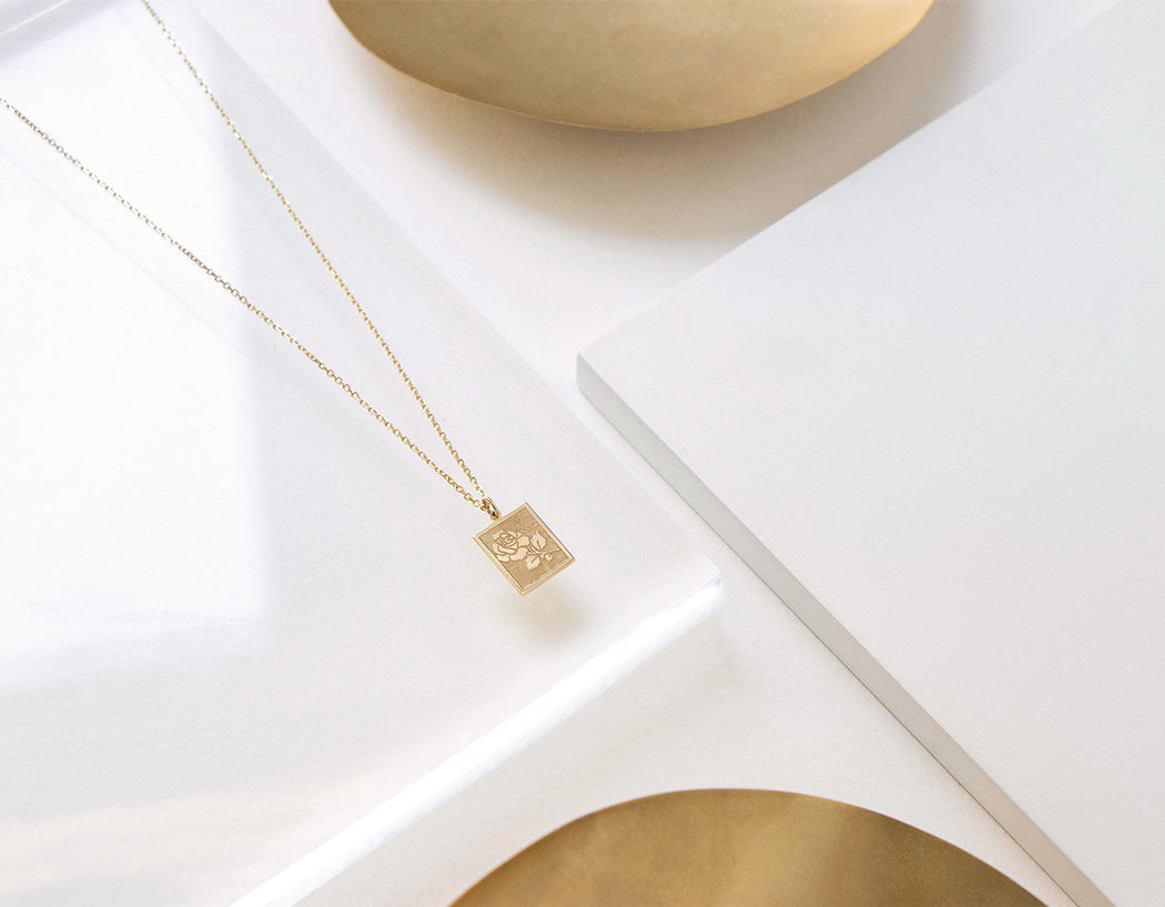 Close up Rose Pendant Necklace on 14k solid gold thin chain white background