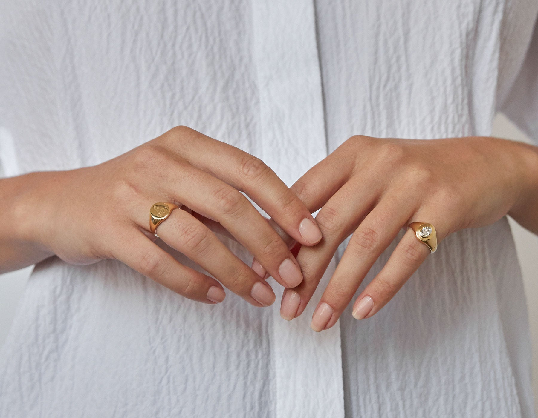 Model wearing Vrai 14k yellow gold signet ring with engraved initial and diamond