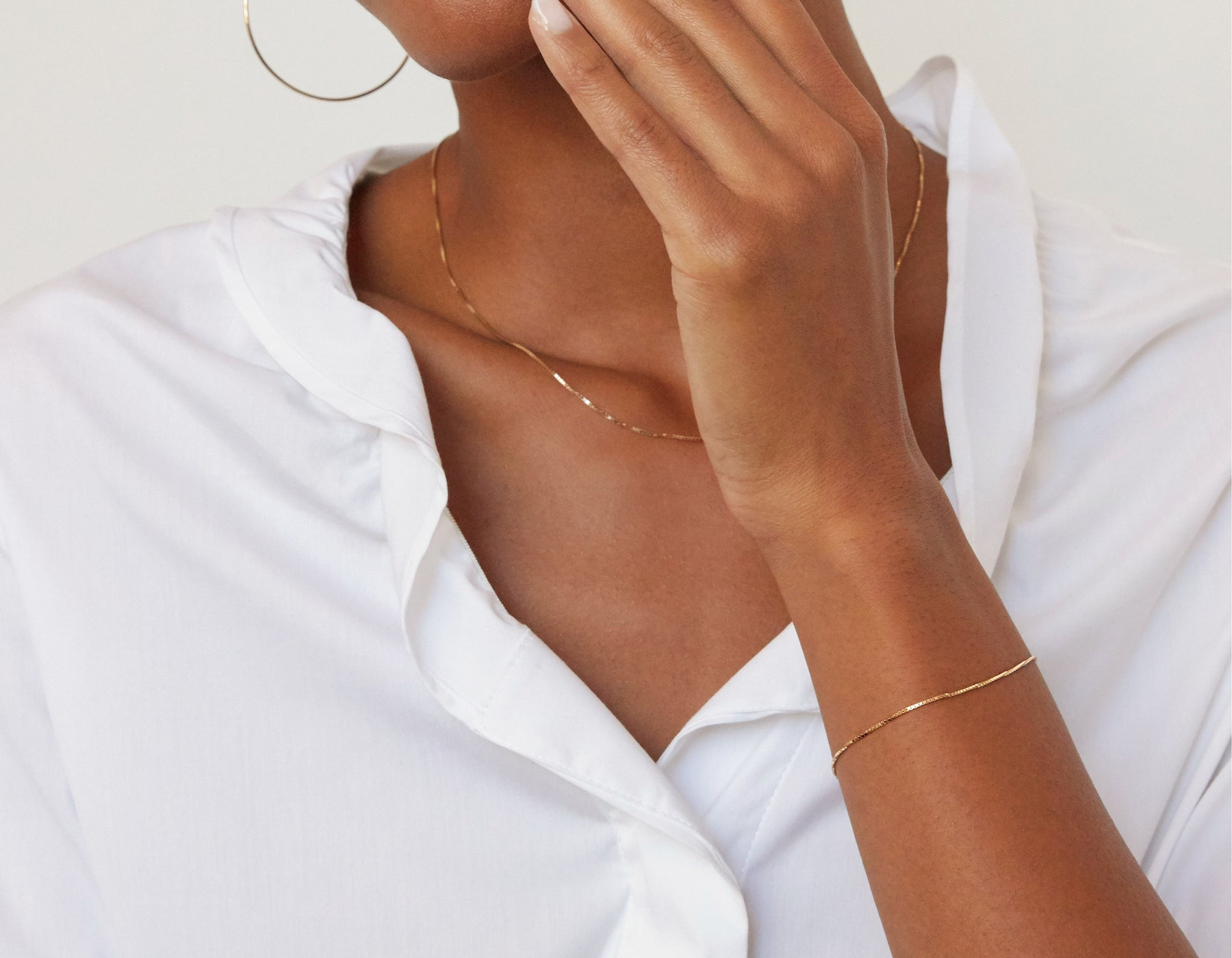 Model wearing Vrai 14k solid gold Silk Box Bracelet diamond cut chain simple classic