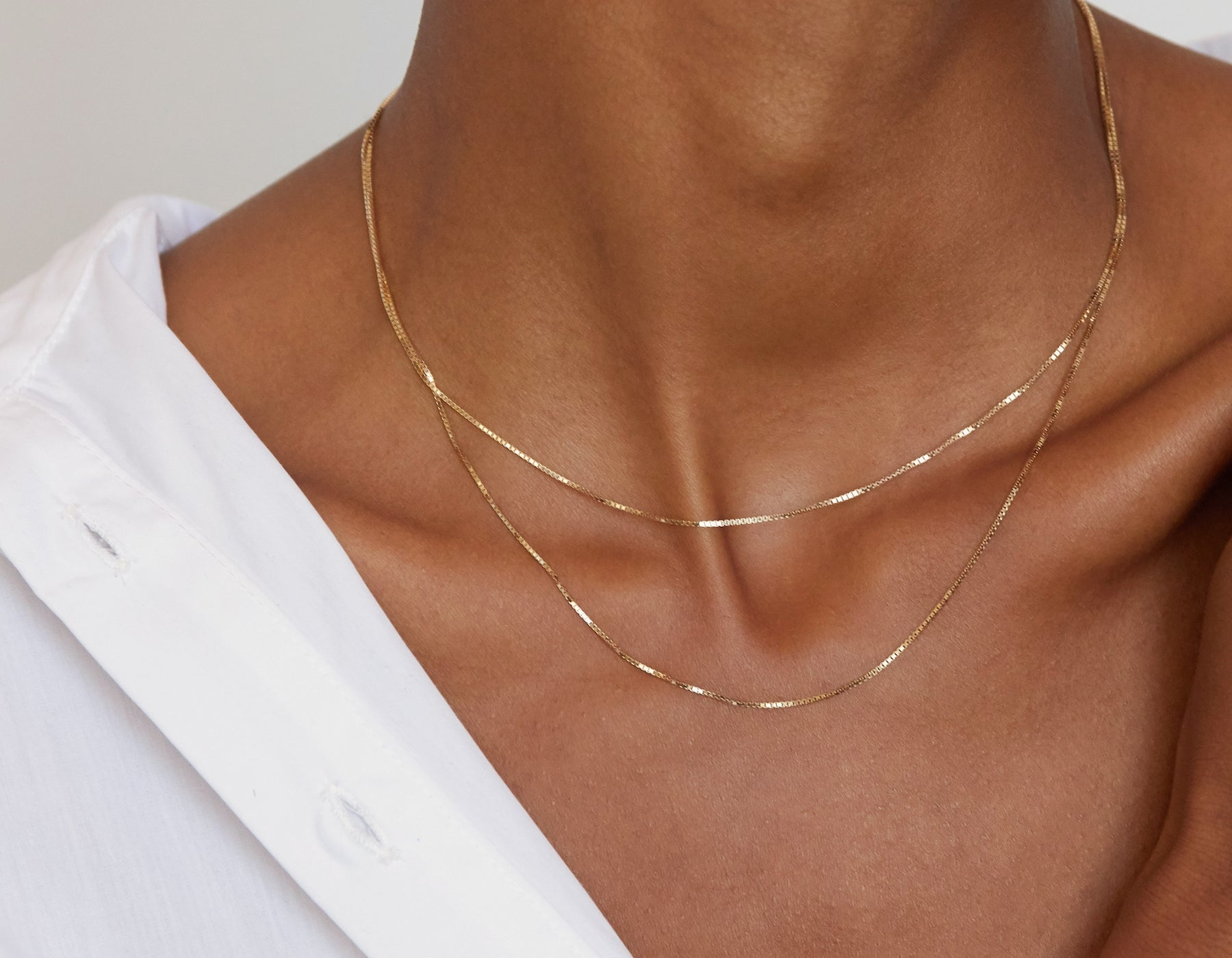 Model wearing Vrai 14k solid gold Silk Box Chain necklace diamond cut chain simple classic