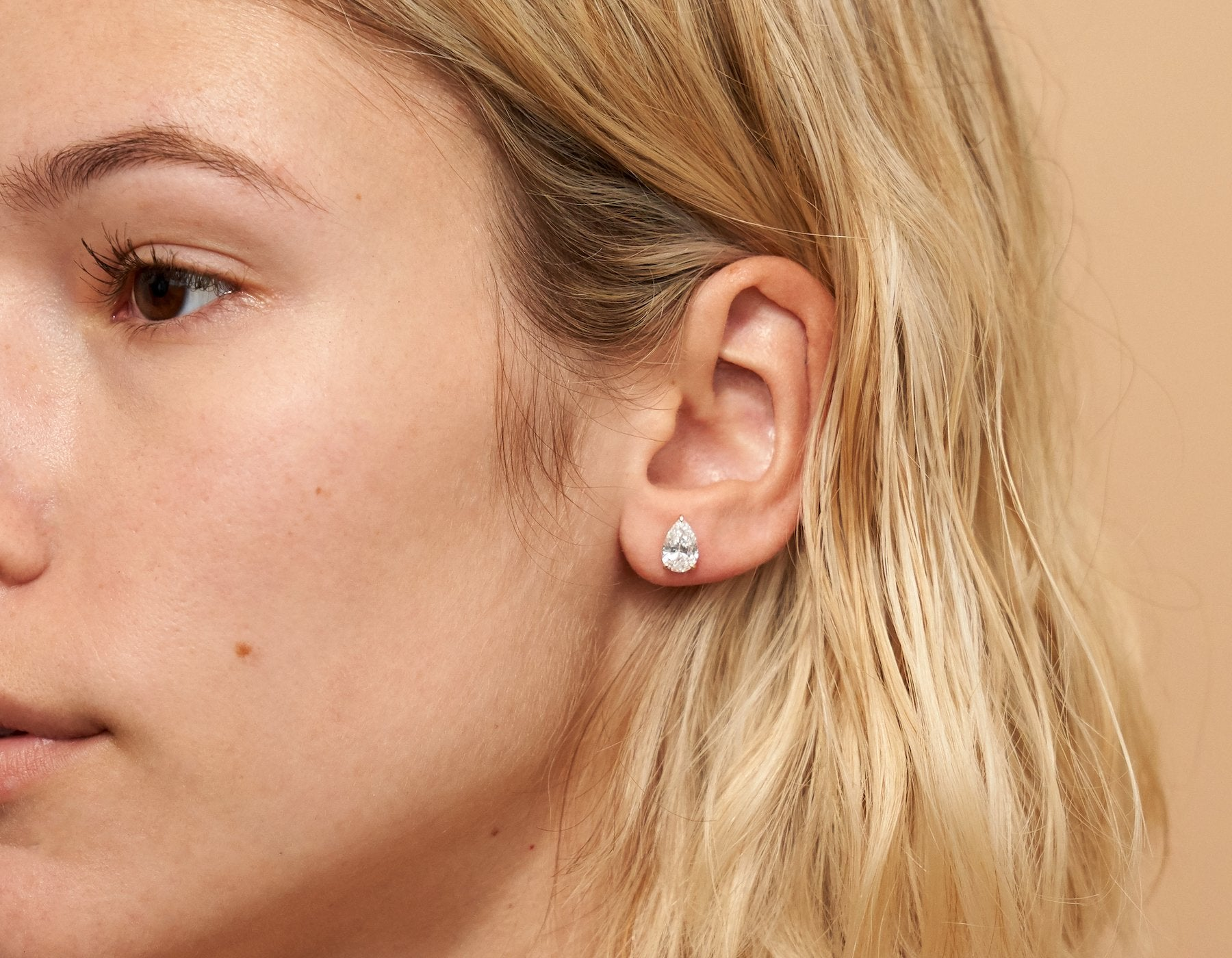 Model wearing Vrai 14K solid gold solitaire pear diamond studs earrings 1ct minimalist delicate, 14K Rose Gold