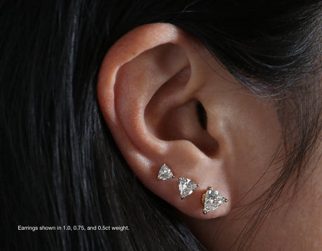 Model wearing Vrai Solitaire Trillion Diamond Studs sustainably created triangle diamonds prong set comparison shot of 1ct .75ct and .5ct diamond earrings