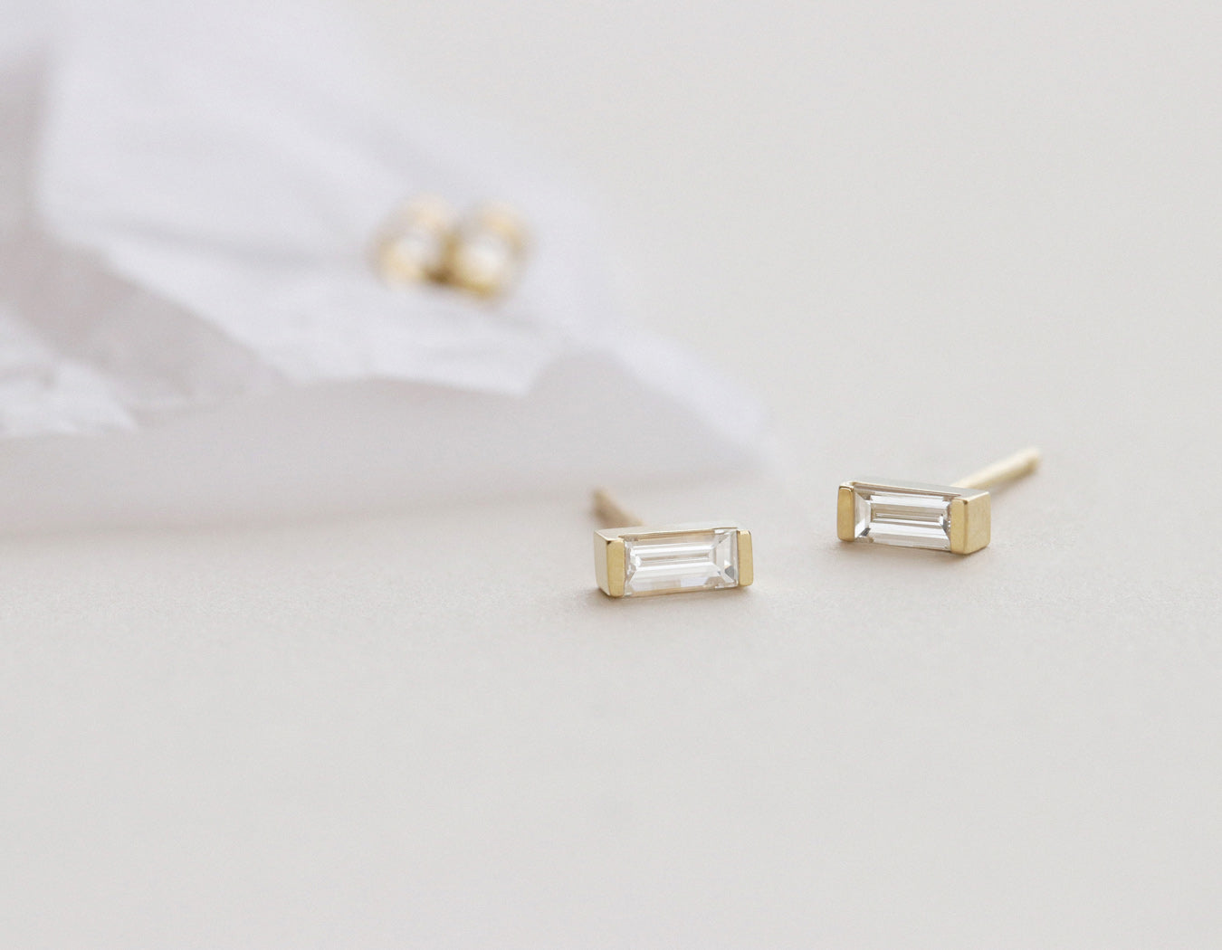Close up of minimalist Baguette Diamond Earrings from Vrai and Oro in 14k yellow gold