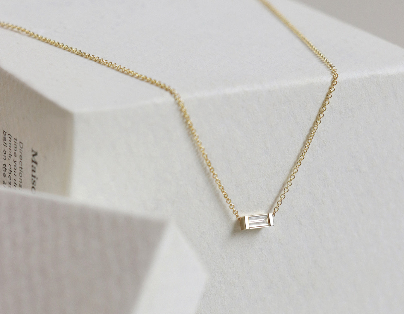 zoom focus of .1 carat Baguette Diamond Necklace in 14k yellow gold by Vrai & Oro hanging off white box