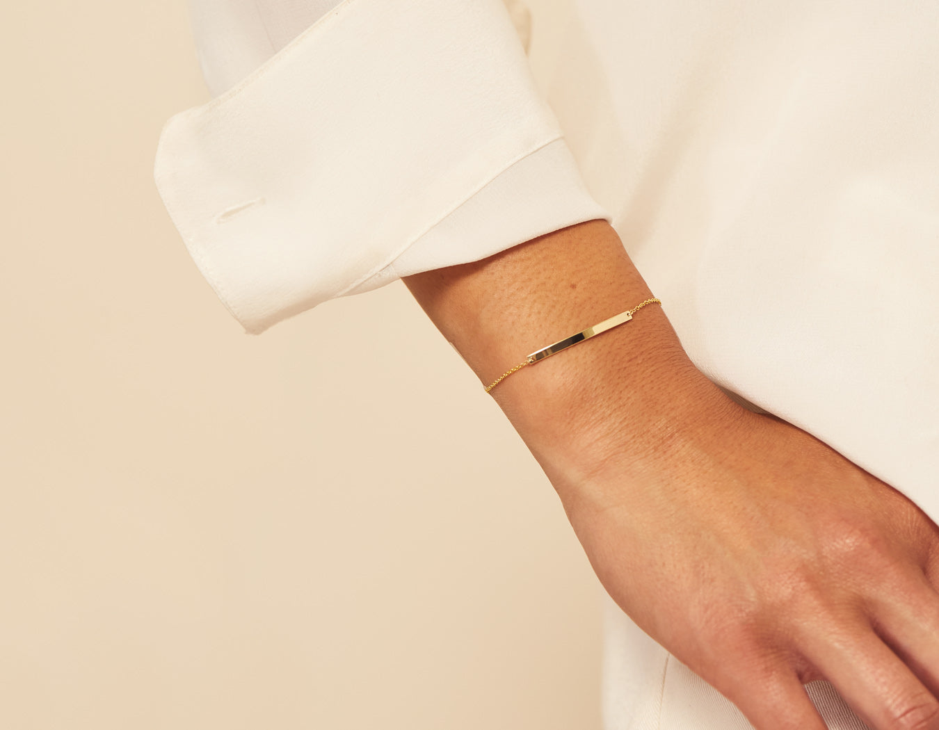 Woman modelling engravable simple 14k solid gold Bar Bracelet in yellow gold by Vrai & Oro