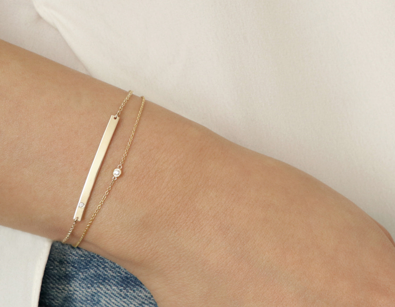 Close up of woman modelling modern minimalist 14k solid gold chain and Bar Bracelet with Diamond by Vrai and Oro