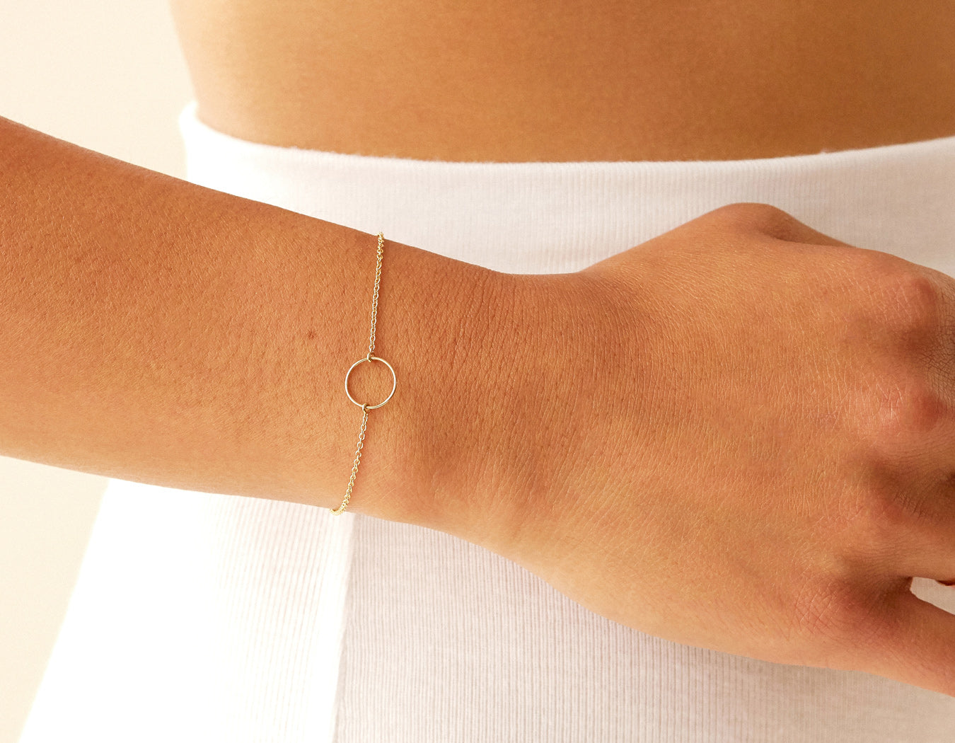 Close up modelling delicate 14k yellow gold Circle Bracelet by Vrai and Oro