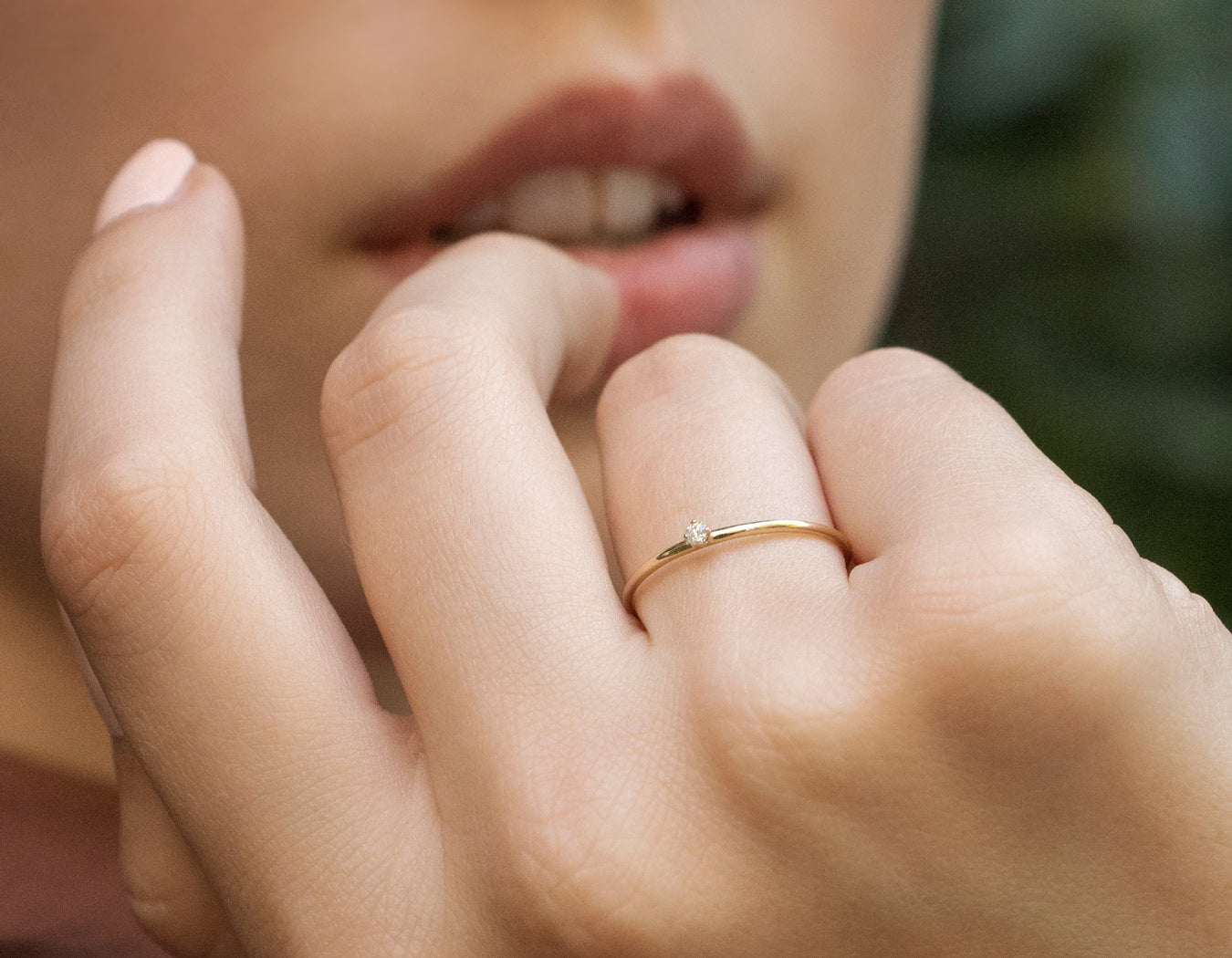 Woman modelling simple sophisticated 14k yellow gold subtle Round Diamond Stacker ring by Vrai & Oro