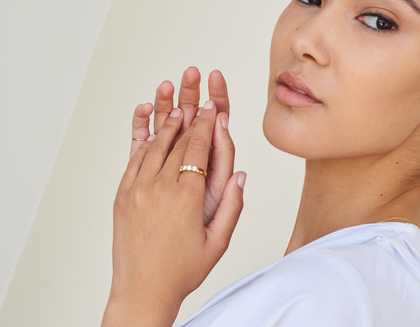 Woman modelling simple classic 14k yellow gold Round Tetrad Band diamond ring by Vrai & Oro minimalist jewelry