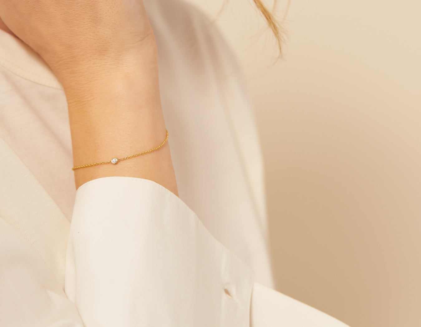 Model wearing simple classic Solitaire Bracelet delicate chain lobster clasp 14k yellow gold .04 ct round diamond Vrai & Oro, 14K White Gold