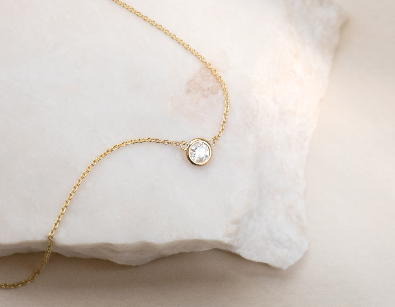 close up simple elegant Solitaire Necklace bezel set .1 carat round brilliant diamond Vrai & Oro modeled on granite