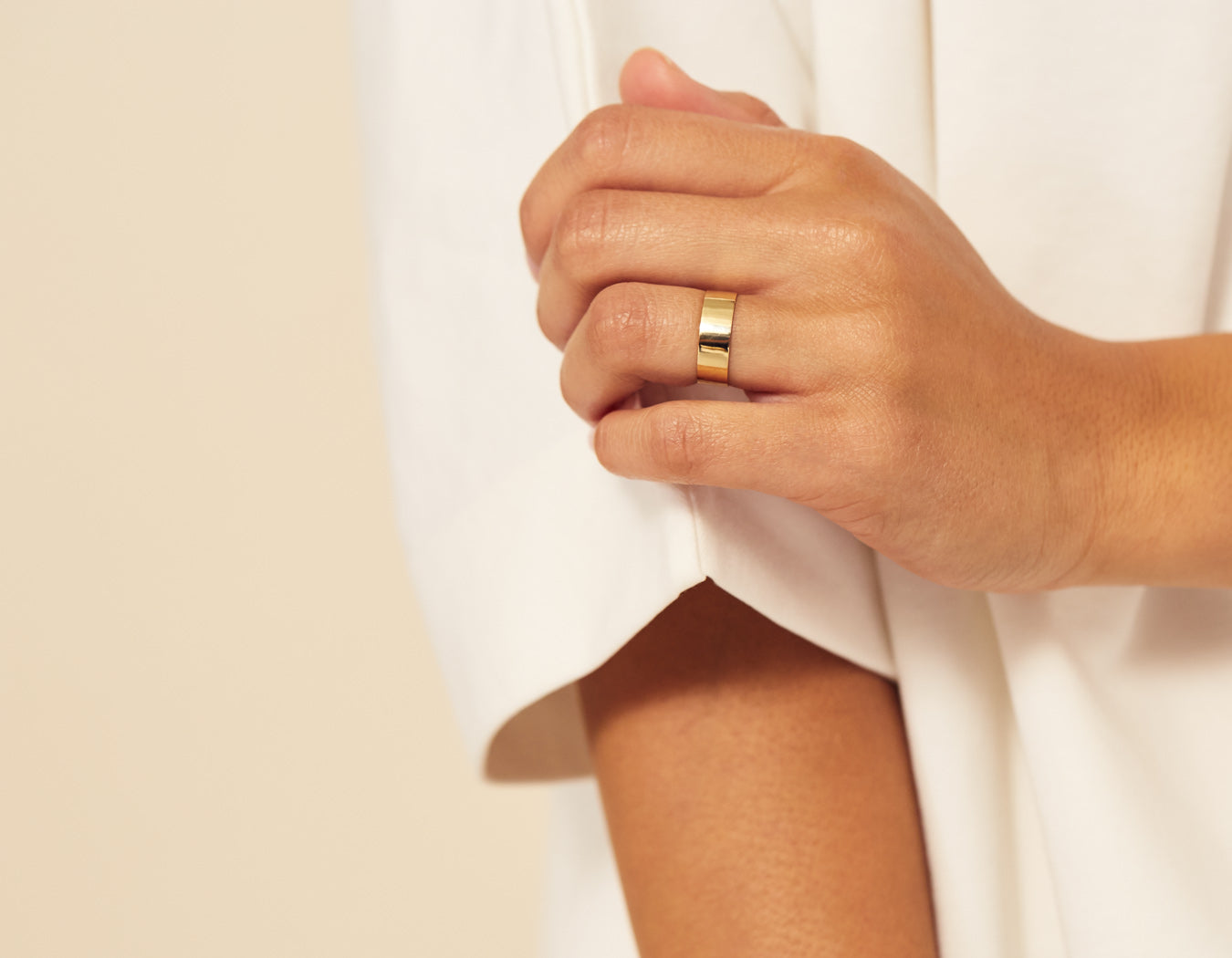 Close up on hand model wearing modern minimalist Thick Stacking Ring in 14k yellow gold Vrai and Oro