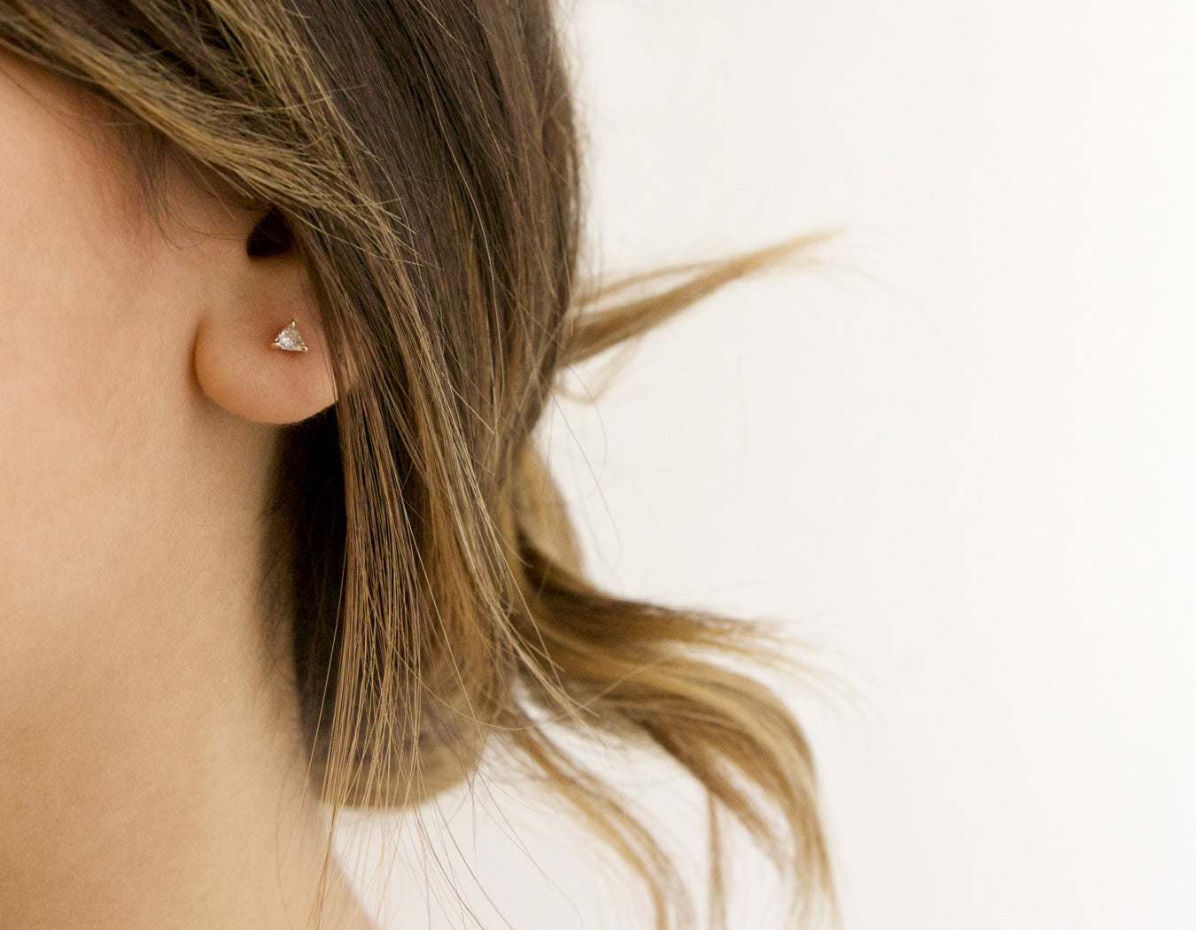 Blonde model wearing simple modern 14k yellow gold Trillion Diamond Earring studs by Vrai & Oro