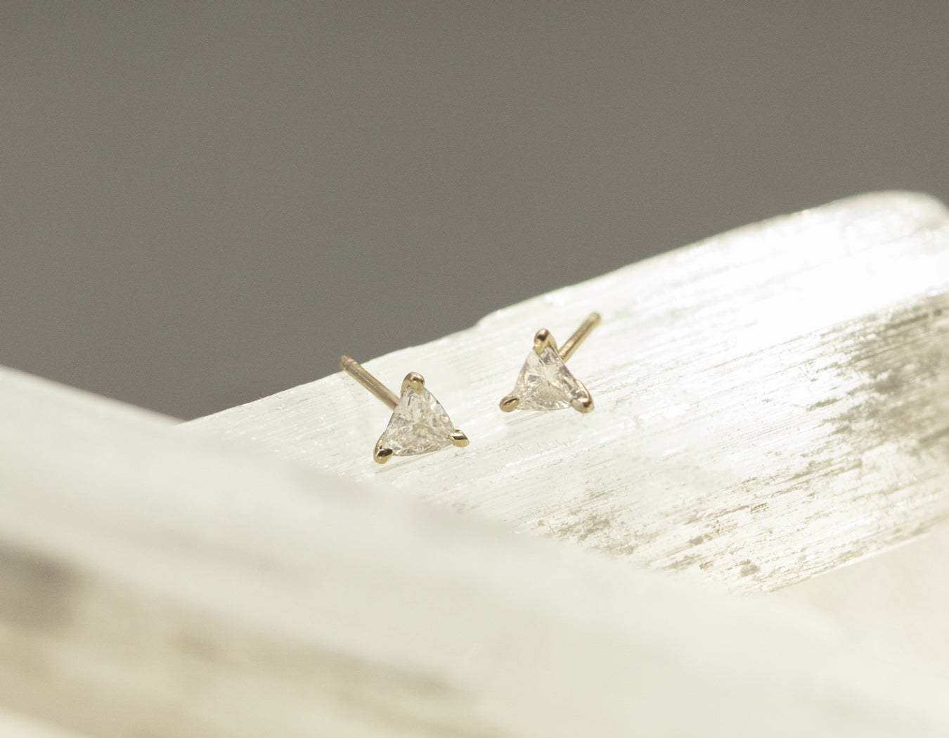 Close up of subtle sophisticated 14k yellow gold Trillion Diamond Earring black background by Vrai & Oro