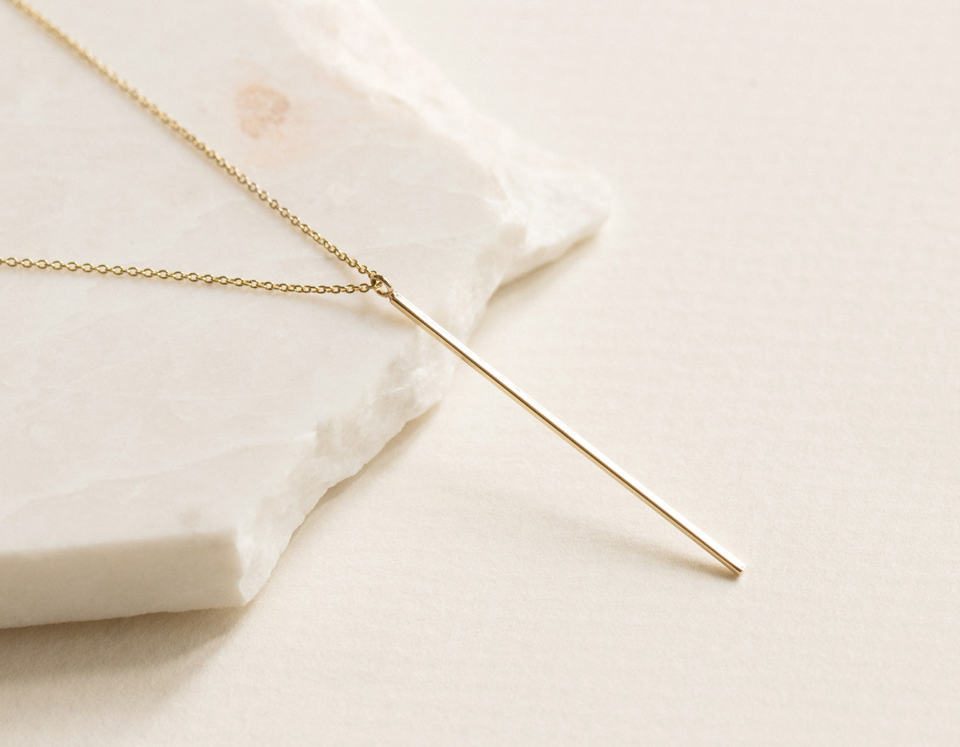 14k yellow gold Vertical Bar Necklace on classic simple chain by Vrai & Oro delicately balanced on white stone