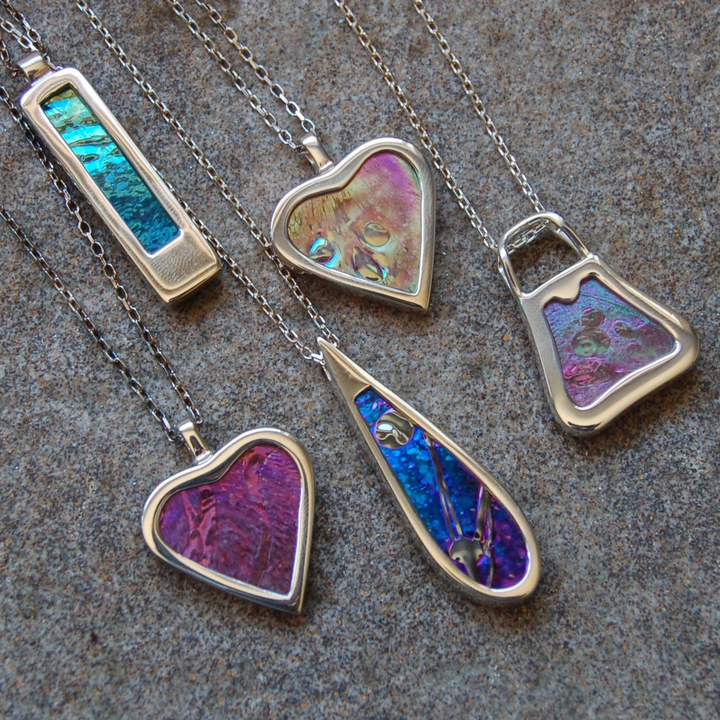 Hallmarked sterling silver pendants with memorial glassand ashes @ £160 each.
