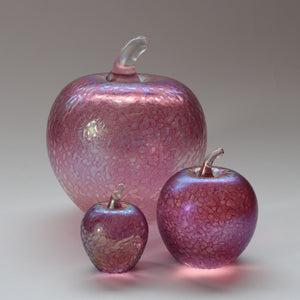 Handmade glass apples in iridescent pink