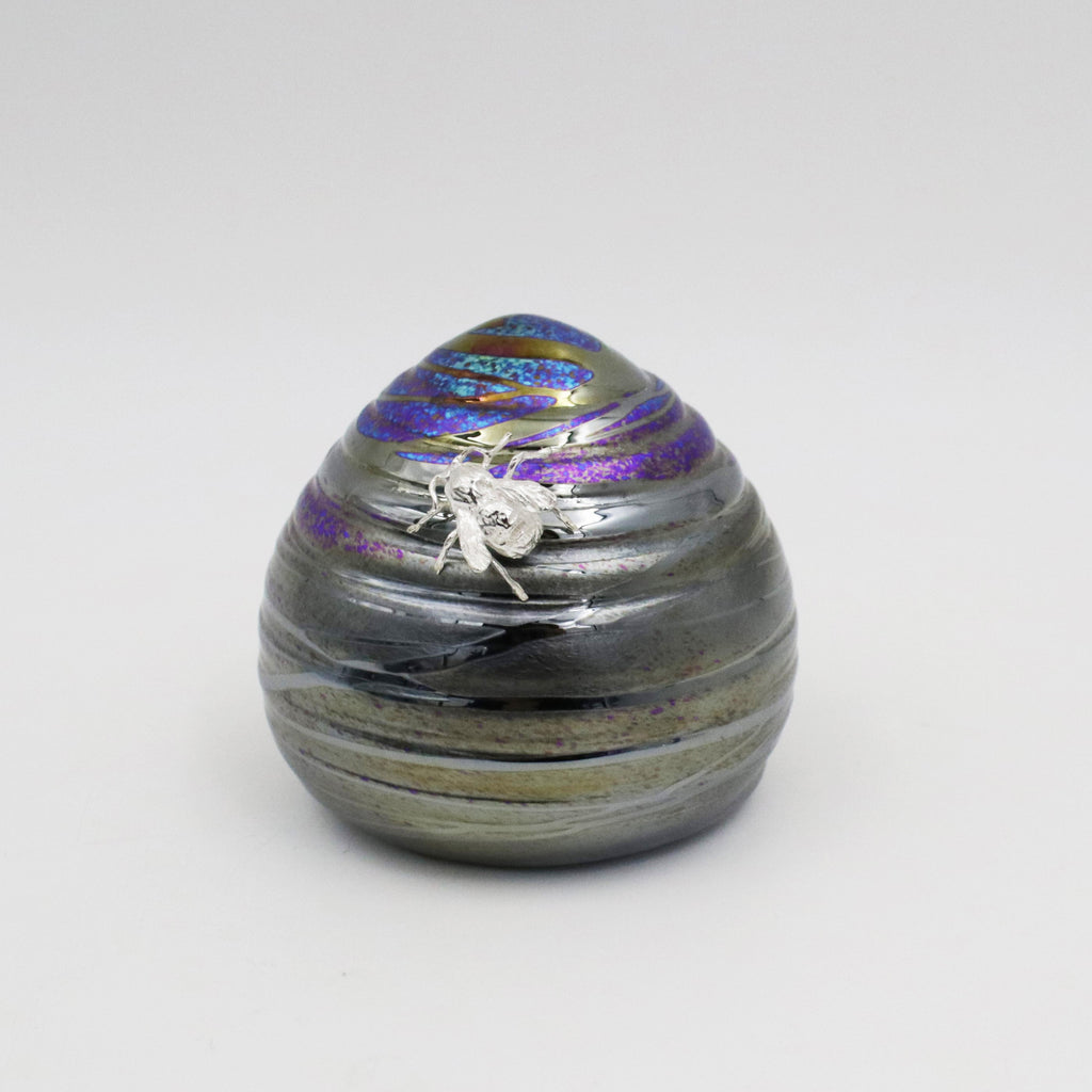 Silver bee resting on a handmade glass skep shaped paperweight