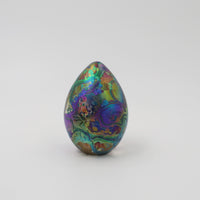 Handmade glass paperweight in the shape of a goose egg in multi coloured iridescense